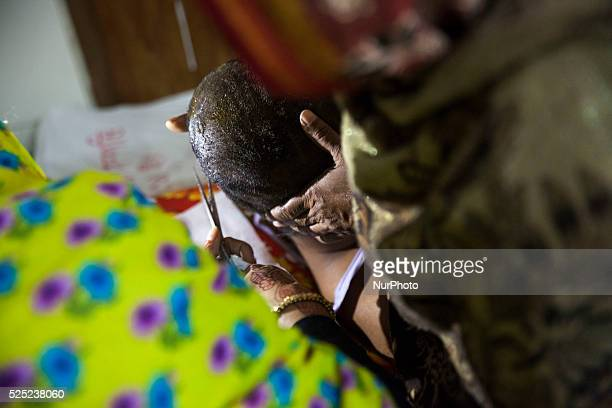 Nazmul Hossain's aunt cutting his hair which were burnt by recent bomb attack in a bus and receives treatment at Dhaka Medical College Hospital...