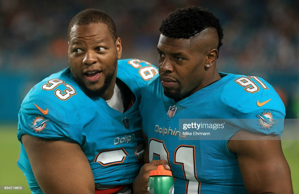 Ndamukong Suh #93 and Cameron Wake #91 of the Miami Dolphins talk during a preseason game against the Baltimore Ravens at Hard Rock Stadium on August 17, 2017 in Miami Gardens, Florida.