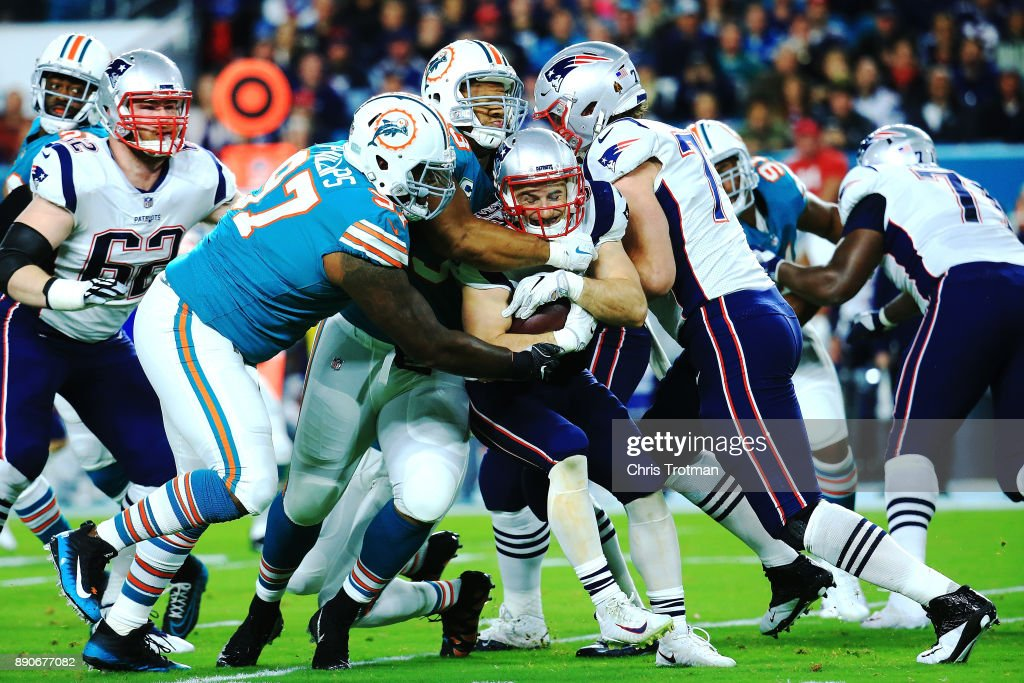 Ndamukong Suh #93 of the Miami Dolphins with the stop on Rex Burkhead #34 of the New England Patriots during the first quarter at Hard Rock Stadium on December 11, 2017 in Miami Gardens, Florida.
