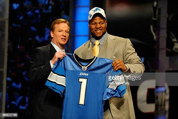 Ndamukong Suh of the Nebraska Cornhuskers stands with NFL Commissioner Roger Goodell as he holds up a Detroit Lions Jersey after Suh was picked...