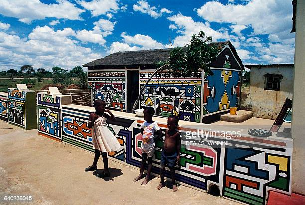 Ndebele children in front of a building decorated with murals in the village KwaNdebele South Africa