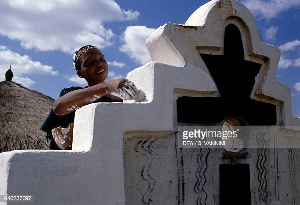 Ndebele woman decorating a village wall Botshabelo township Transvaal South Africa