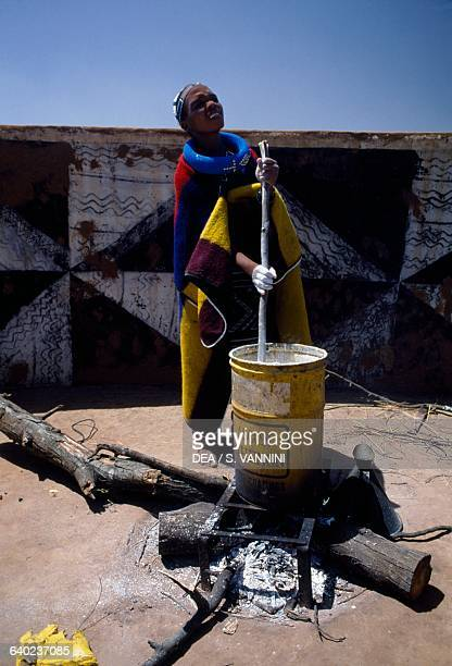 Ndebele woman preparing colours for painting murals in the village Botshabelo township Transvaal South Africa