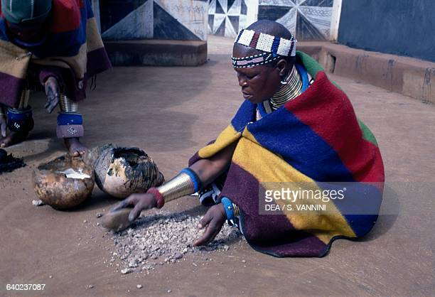 Ndebele woman preparing material for filling the village walls Botshabelo township Transvaal South Africa