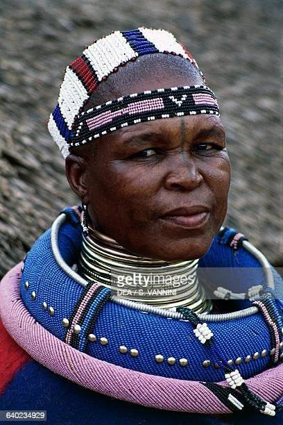 Ndebele woman wearing a traditional costume and idzilla bronze or copper neck rings Ndebele village Botshabelo township Transvaal South Africa