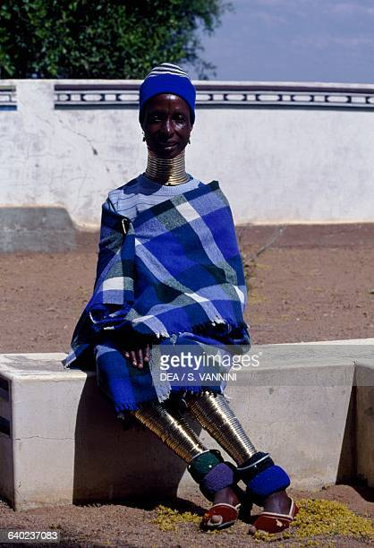 Ndebele woman wearing idzilla bronze or copper neck and leg rings South Africa