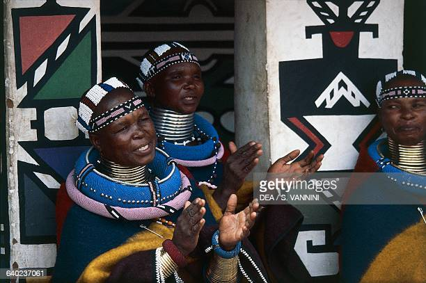Ndebele women wearing traditional costumes and idzilla bronze or copper neck rings Ndebele village Botshabelo township Transvaal South Africa