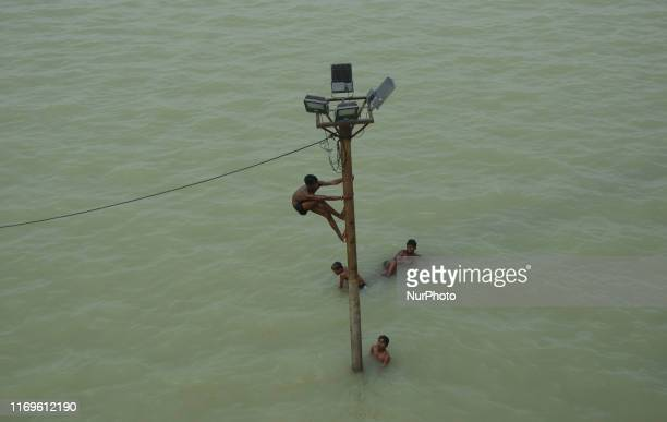 Ndian youths dangle from an electric light poll and power line before diving in to the floodwaters of an overflowing Ganges River , in Allahabad on...