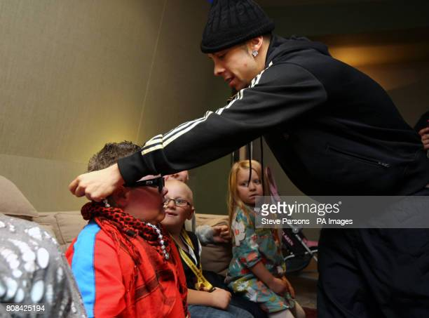 NDubz's Dino 'Dappy' Contostavlos gives some sunglasses to sixyearold Mark Sheppard from Glasgow who visited the Angelic Studios in Brackley after...