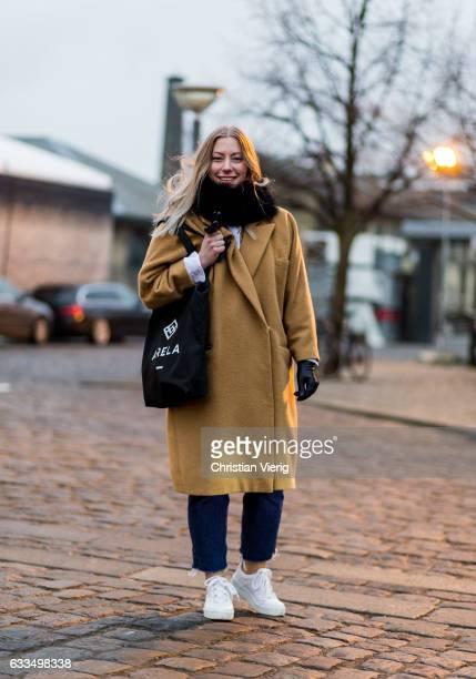 Nea Aspholm wearing an oversized beige coat denim jeans sneaker scarf leather gloves at the Copenhagen Fashion Week Autumn/Winter 17 on February 1...