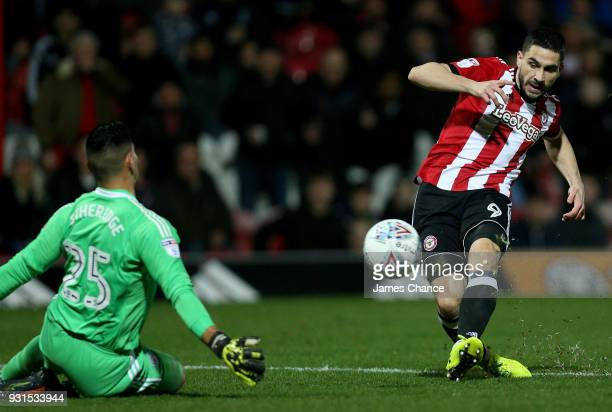 Neal Maupay of Brentford scores his sides first goal past Neil Etheridge of Cardiff City during the Sky Bet Championship match between Brentford and...