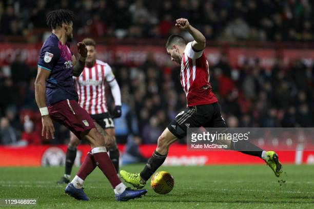 Neal Maupay of Brentford shoots and scores his side's first goal during the Sky Bet Championship match between Brentford and Aston Villa at Griffin...