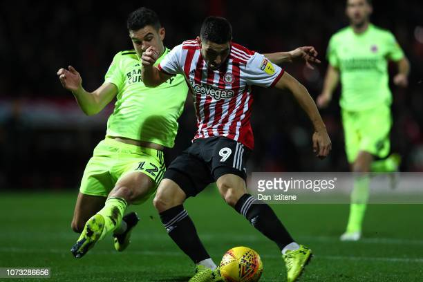 Neal Maupay of Brentford shoots past John Egan of Sheffield United to score the opening goal during the Sky Bet Championship match between Brentford...