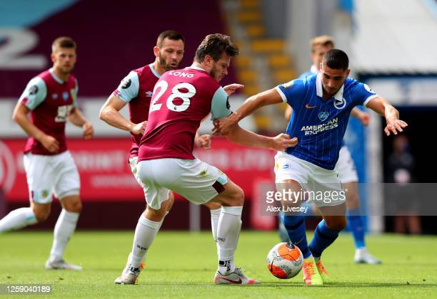 Neal Maupay of Brighton and Hove Albion and Kevin Long of Burnley challenge for the ball during the Premier League match between Burnley FC and...
