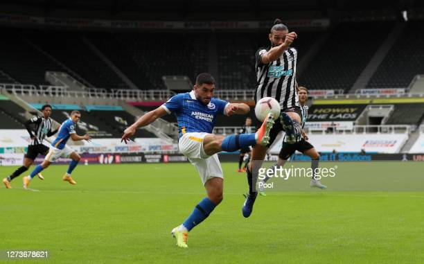 Neal Maupay of Brighton and Hove Albion clears with pressure from Andy Carroll of Newcastle United during the Premier League match between Newcastle...