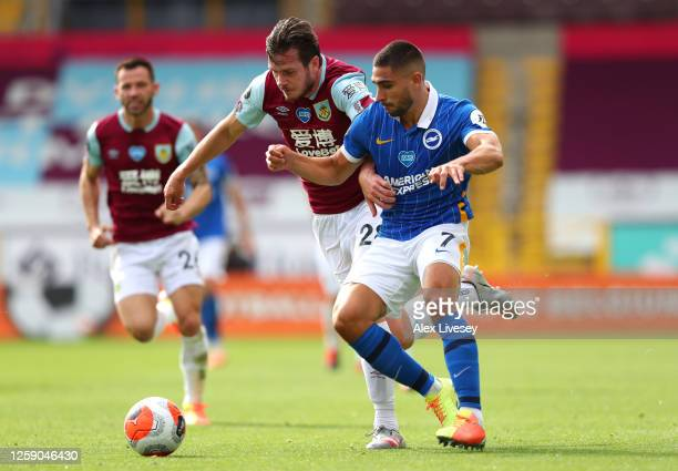 Neal Maupay of Brighton and Hove Albion is challenged by Kevin Long of Burnley during the Premier League match between Burnley FC and Brighton Hove...