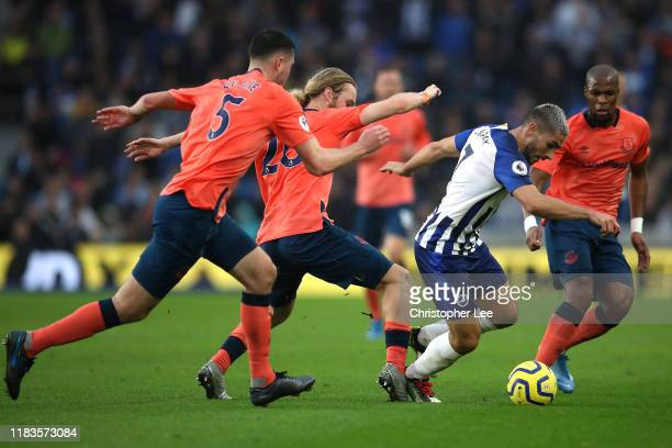 Neal Maupay of Brighton and Hove Albion is challenged by Michael Keane, Tom Davies, and Djibril Sidibe of Everton during the Premier League match...