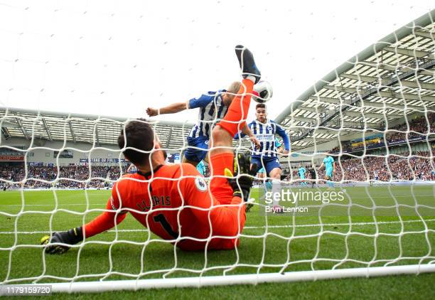 Neal Maupay of Brighton and Hove Albion scores his sides first goal past Hugo Lloris of Tottenham Hotspur who goes down injured during the Premier...