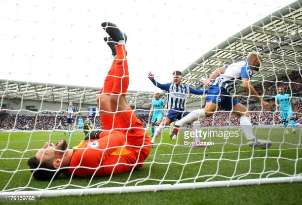 Neal Maupay of Brighton and Hove Albion scores his sides first goal past Hugo Lloris of Tottenham Hotspur, who goes down injured during the Premier...