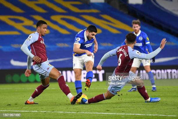 Neal Maupay of Brighton & Hove Albion shoots whilst under pressure from Ezri Konsa and Douglas Luiz of Aston Villa during the Premier League match...