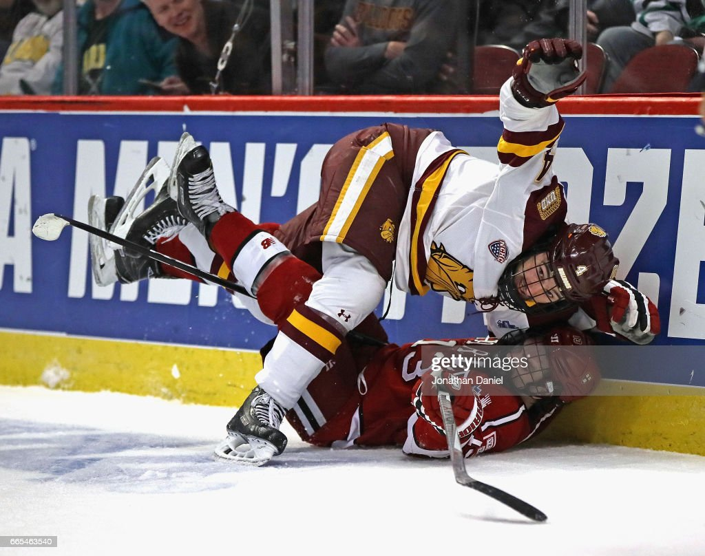 Neal Pionk #4 of the Minnesota-Duluth Bulldogs and Nathan Krusko #13 of the Harvard Crimson get tangled up along the boards during game one of the 2017 NCAA Division I Men's Hockey Championship Semifinal at the United Center on April 6, 2017 in Chicago, Illinois.