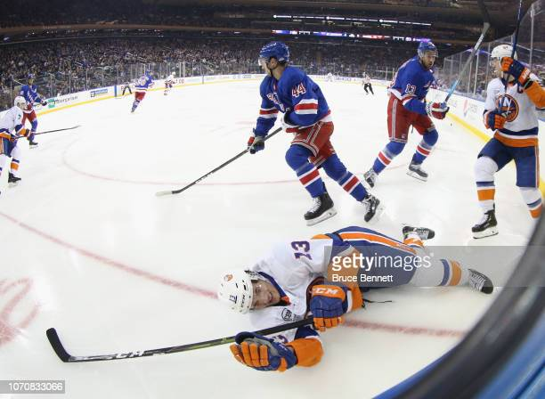 Neal Pionk of the New York Rangers checks Mathew Barzal of the New York Islanders during the third period at Madison Square Garden on November 21...