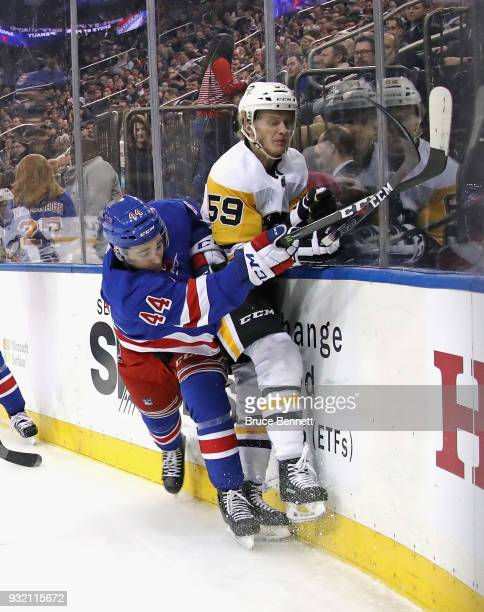 Neal Pionk of the New York Rangers hits Jake Guentzel of the Pittsburgh Penguins into the boards during the first period at Madison Square Garden on...
