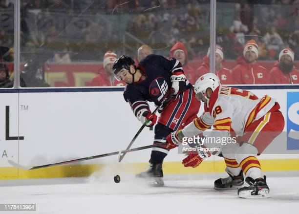 Neal Pionk of the Winnipeg Jets gets a shot off with pressure from Oliver Kylington of the Calgary Flames during the 2019 Tim Hortons NHL Heritage...