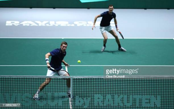 Neal Skupski of Great Britain plays a backhand shot as his playing partner Jamie Murray looks on during their Davis Cup Group Stage match against...
