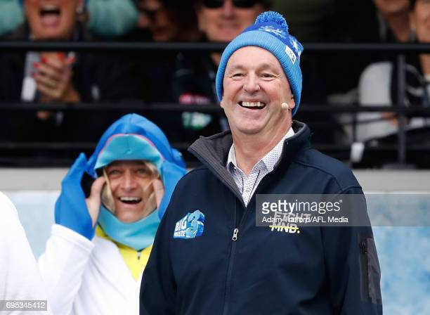 Neale Daniher reacts after Andrew Gaze heads down the slide for the Big Freeze MND fundraiser during the 2017 AFL round 12 match between the...