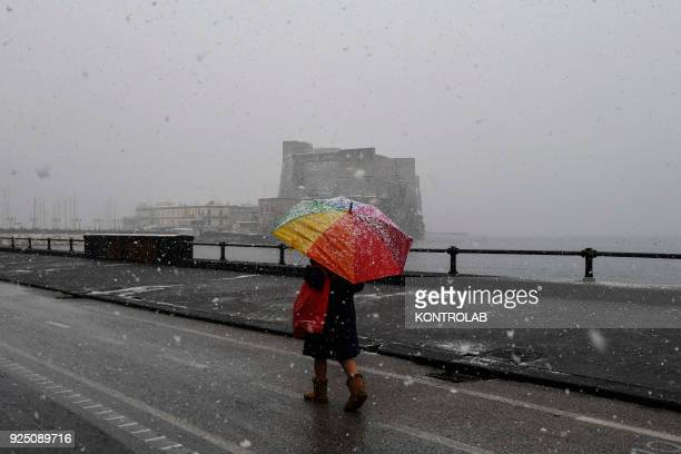 Neapolitan citizens walk on snowy roads front sea during the extraordinary snowfall that has whitened the city Bad weather comes from the Siberian...