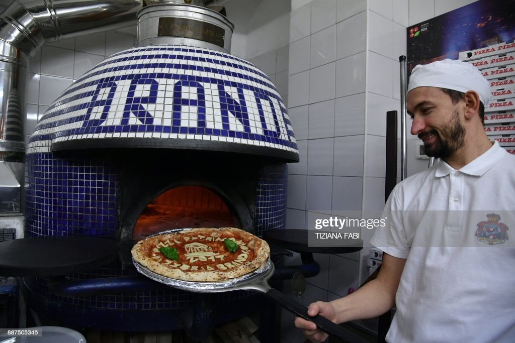 A Neapolitan pizza maker poses next to the oven with a pizza celebrating the Unesco decision to make the art of Neapolitan 'Pizzaiuolo' an 'intangible heritage', on December 7, 2017 at the Pizzeria Brandi in Naples. The art of the Neapolitan Pizzaiuolo is a culinary practice consisting of four different phases relating to the preparation of the dough and its baking in a wood-fired oven. The practice originates in Naples, where around 3,000 Pizzaiuoli now live and perform, and plays a key role in fostering social gatherings and intergenerational exchange. / AFP PHOTO / Tiziana FABI