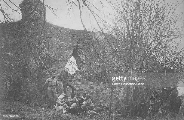 Near a stone wall, Austrian military soldiers and refugee family in the woods during World War I, Austria, 1918.