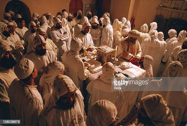 Near Bir Hooker Coptic Monastery of St BishoyIn deep contemplation the Coptic monks wearing white symbol color of the purity of the angels kneel...