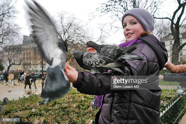 CONTENT] Near Notre Dame Paris France a girl feeds pigeons that fly onto her hands