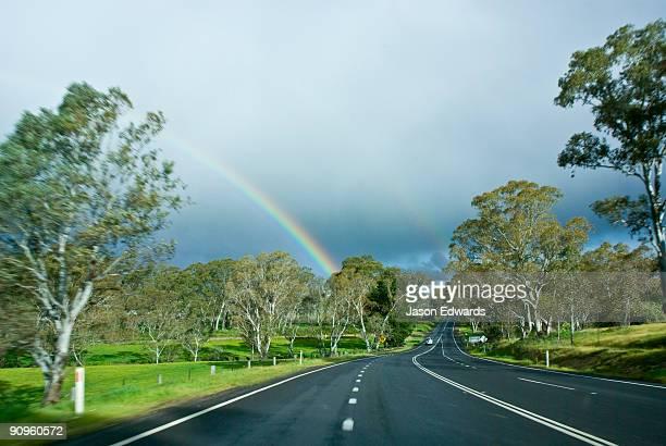A car drives towards a rainbow over farmland on a country road.
