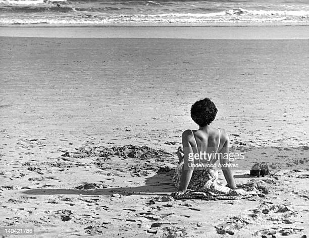 Near the end of the day a woman sitting on the beach leans back and watches the waves come in Atlantic City New Jersey circa 1936