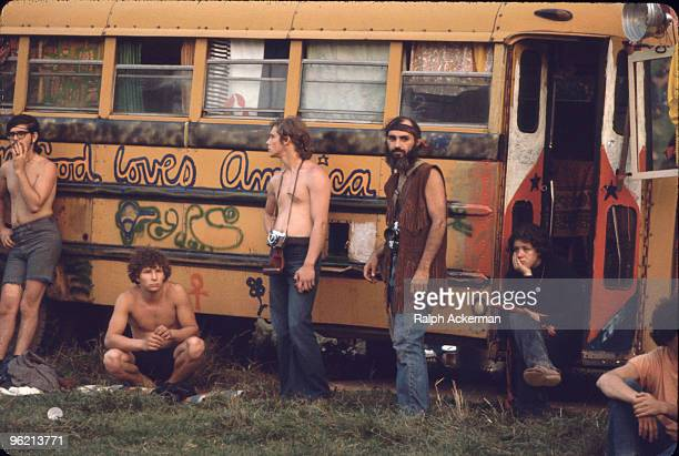 Near the 'Free Stage' at the Woodstock Music and Arts Fair several men two with cameras around their necks lean against a decorated school bus used...
