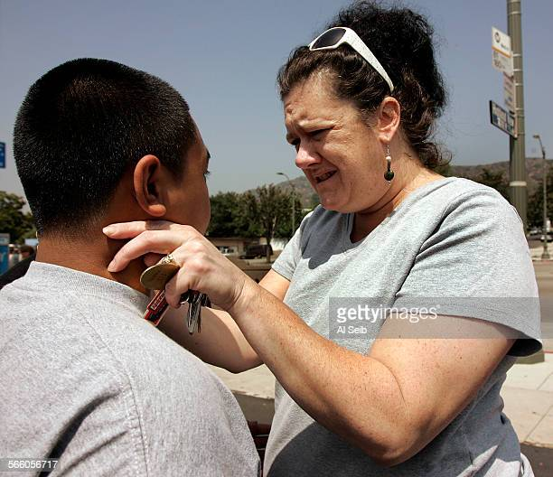 Nearby resident Heidi Vankempen who was on the crash scene last night comforts Niko Medonza 17 and other Eagle Rock High School classmates as they...