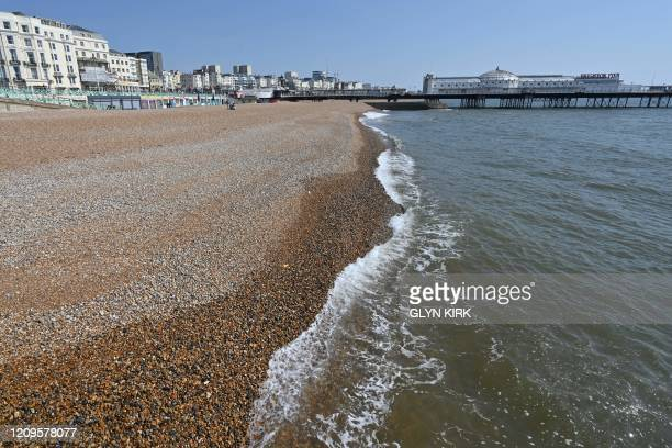 A neardeserted beach is pictured looking east towards the Palace Pier in Brighton on the south coast of England on April 10 2020 as warm weather...