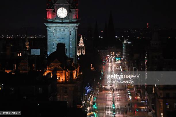 Near-deserted Princes Street in Edinburgh is pictured as the time passes midnight, shown on the Balmoral Hotel clock early on January 1, 2021 in...