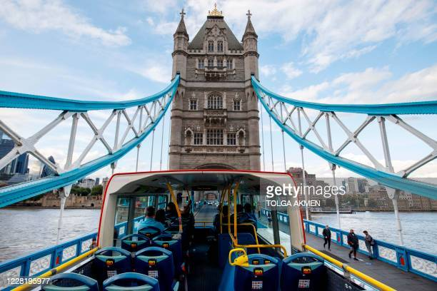 Near-empty open-top tourist tour bus crosses Tower Bridge in central London on August 24, 2020. - For those tourists who do run the gauntlet of...