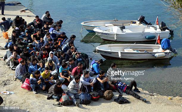 Nearly 150 asylum seekers arrested in a people smuggling operation carried by Turkish security forces wait on Tuesday October 29 2013 in Bodrum...