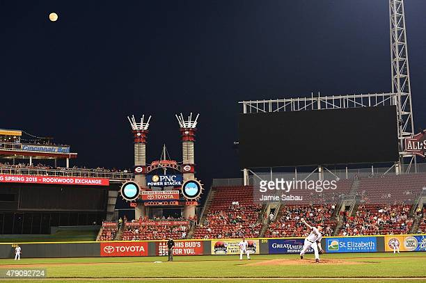 A nearly full moon hangs over the ballpark as Anthony DeSclafani of the Cincinnati Reds pitches in the second inning against the Minnesota Twins at...