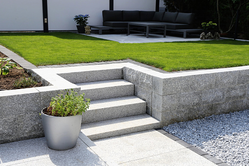 Neat and tidy garden with granite wall and solid block steps 1074265062