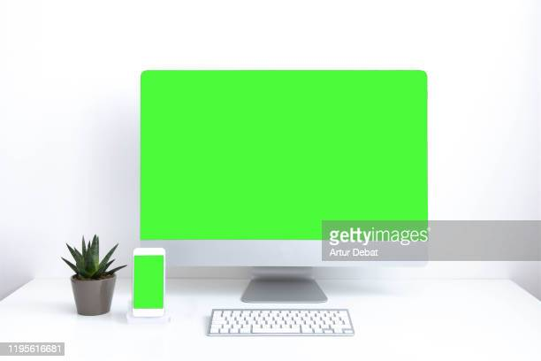 neat white office composition with big screen computer and mobile phone in green screen. - chroma key foto e immagini stock