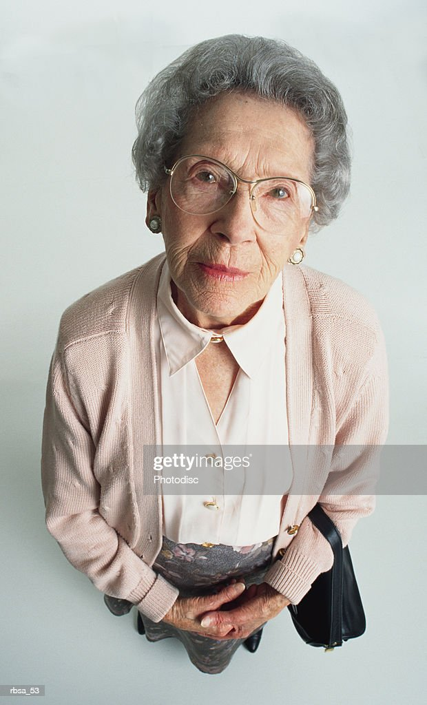 neatly dressed old caucasian gray haired adult female with glasses wearing a pale pink sweater and gray skirt looks up at the camera with an expression of strictness and concern : Stockfoto