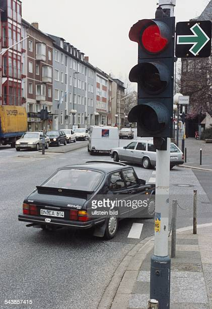 Neben einer auf rot geschalteten Ampel weist ein grüner Pfeil daraufhin, dass Autofahrern das Abbiegen dennoch erlaubt ist. Auto, Verkehrsteilnehmer,...