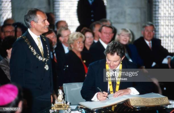 Neben Oberbügermeister Jürgen Unden trägt sich Tony Blair anlässlich der Verleihung des Karlspreises der Stadt Aachen in das Goldene Buch am 13. Mai...