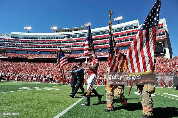 Nebraska Cornhuskers defensive end Tyrone Fahie carries the American Flag onto the field before their game against the Idaho Vandals at Memorial...